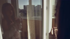 Seductive girl standing with a cup of tea in her hands on the balcony Stock Footage