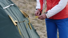Woman unties the rope and stretch the tent Stock Footage