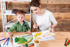 Cute little boy and his mother paiting bright pictures together Stock Photos