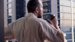 Young man in bathrobe drinking coffee and admire view standing on balcony  Stock Footage