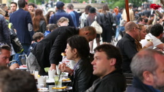 Milan crowd people tourists sit rest eating drinking at street restaurant tables Stock Footage
