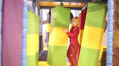 Small girl playing in children's playroom. A lot of colorful equipment are in th - stock footage