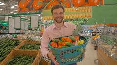 Joyful man holding basket of fresh vegetables Stock Footage