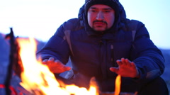 A man warms his hands by the fire from the cold Stock Footage