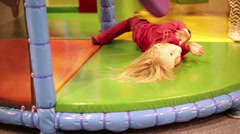 Small girl playing in children's playroom lying on the floor. - stock footage