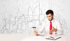 Businessman sitting at the white table with hand drawn buildings Stock Photos