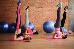 Pretty sporty girls are exercising in gym - stock photo