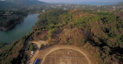 Soccer Game On Pitch Overlooking Rawai in Phuket Aerial Approach Shot Stock Footage