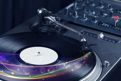 Turntable playing vinyl with glowing abstract lines - stock photo