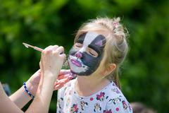 Cute little five years old girl, having her face painted as kitten on her bir Stock Photos
