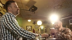 Cheerful stylish man drinking draft beer at bar counter in pub 4K UHD video. - stock footage