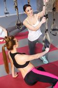 Cheerful two girls are adjusting sport equipment - stock photo