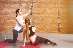 Pretty sporty women are fixing elastic rope - stock photo