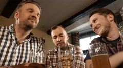 Best friends having fun watching football and drinking beer in pub 4K UHD video Stock Footage