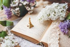 Still life with lilac flowers, book, lace bookmark and miniture Eiffel tower. - stock photo