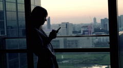 Silhouette of woman in bathrobe using smartphone standing by window at home Stock Footage