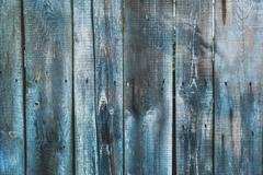 Wooden background of old fence with rusty nails. Shabby texture of blue color Stock Photos