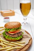 Hamburger with grilled marbled beef, tomato, cheese, salad and fries Stock Photos