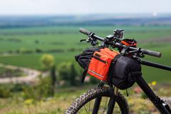 Bicycle with orange bags for travel - stock photo