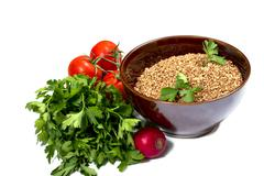 Plate with buckwheat, parsley, a garden radish, tomatoes Stock Photos