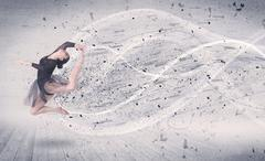 Performance ballet dancer jumping with energy explosion particles Stock Photos
