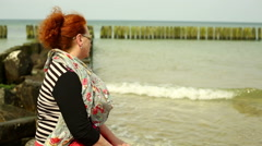Sad woman spends time near sea - stock footage