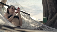 Young woman using smartphone while lying on hammock on beach Stock Footage
