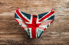 Panties with english flag pattern attached to rope with clothespins on wooden Stock Photos