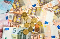Euro banknotes and coins scattered over the table Stock Photos
