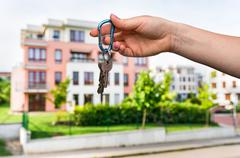 Real estate agent giving house keys to a new property owner on blurred backgr - stock photo