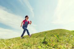 happy little girl running on green summer field - stock photo