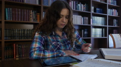 A student sits in the library and preparing for University exams. 4K Stock Footage