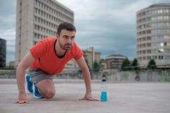 Young adult sportsman working out in the city Stock Photos