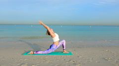 Woman doing yoga by the sea Stock Footage