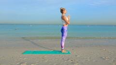 Woman do yoga still asana on the beach - stock footage