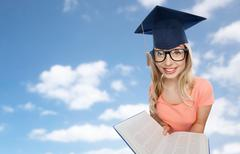 student woman in mortarboard with encyclopedia - stock photo