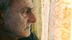 Sad and melancholic old man looks to the window Stock Footage