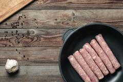Raw Sausages in a Pan Stock Photos