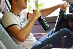 Man drinking beer while driving the car - stock photo