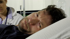 Doctor trying to comfort sick sad patient in bed in hospital Stock Footage