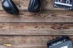 Cassette tapes, cassette player and headphones over wooden table. top view - stock photo