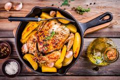 Roasted whole chicken with potatoes and thyme - stock photo