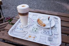 Latte in glass cup and cookie and sugar on a saucer on colorful tray. Close u - stock photo