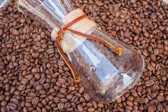 Glass vessel dip in pile of coffee beans. Background. Stock Photos