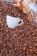 Glass vessel and coffee mug on pile of coffee beans. Background. - stock photo