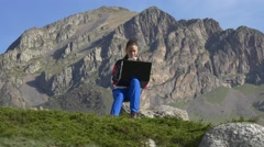 Young girl with laptop on the background of formidable cliffs Stock Footage