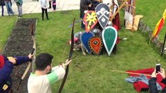 Historical reconstruction men shooting bows with arrows to knights behind Stock Footage