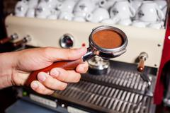 Someone holdinh part of coffee machine with grind coffe beans. Close up Stock Photos