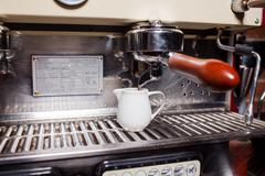Coffee machine pouring hot coffee into porcelain mug. Close up. - stock photo