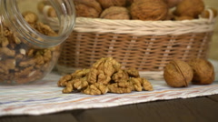 Walnut in basket and walnuts kernels on old wooden table. Stock Footage